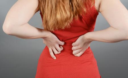 Young woman having back pain, lumbago, sciatica