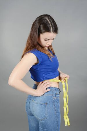 sceptic: young woman measuring waist with tape measure Stock Photo
