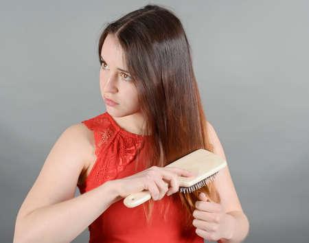 giovane donna: Giovane donna che spazzola i suoi capelli