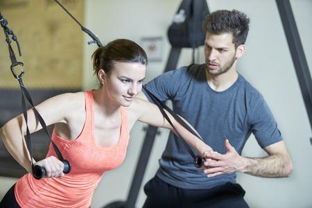hombre fuerte: Pareja en el gimnasio en el entrenamiento de suspensi�n