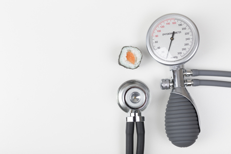 blood pressure gauge: Health checkup with blood pressure gauge and stethoscope, sushi Stock Photo