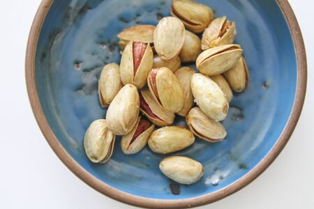 safran: Lemon and safran roasted salted pistachios in a blue bowl