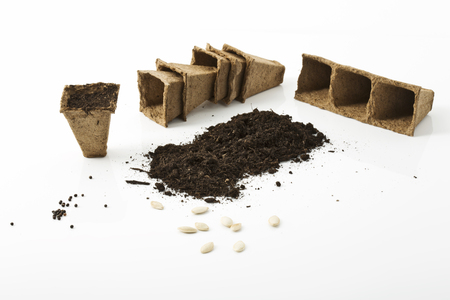 turba: Suelos, macetas de turba y semillas en el fondo blanco Foto de archivo