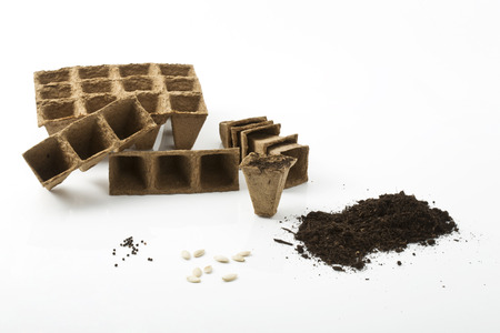 seed pots: Soil, peat pots and seeds on white background
