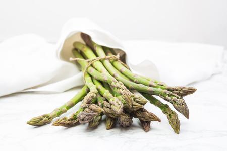 white napkin: Organic green asparagus wrapped in white napkin Stock Photo