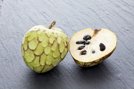 grijze achtergrond: Whole and half cherimoyas on gray background Stockfoto