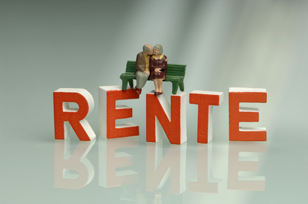 Figurine  sitting on bench, on top of writing Rente