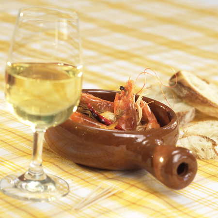 Prawns in bowl with glass of wine on table photo