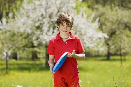 flying disc: Germany, Baden Württemberg, Tübingen, Boy (11)  holding frisbee, smiling, portrait