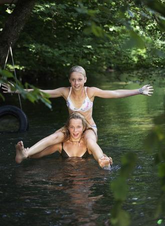 bathe: Two teenage girls (13-14) bathing in river Stock Photo