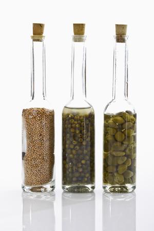 alcaparras: Botellas con granos de mostaza, pimiento verde y las alcaparras