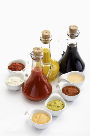 Glass bottles and bowls with different sauces
