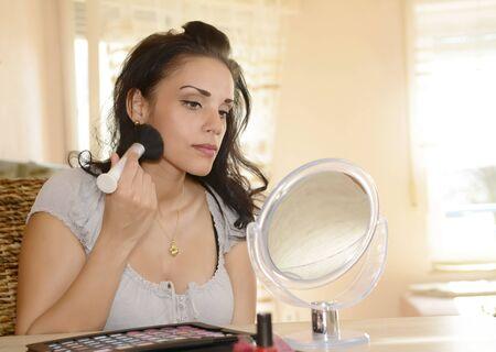 mujer maquillandose: Joven aplicar maquillaje con pincel