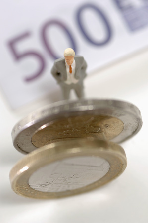 male likeness: Figurine by coins and banknotes Stock Photo
