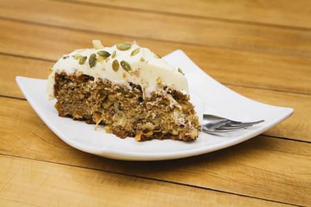 Piece of carrot cake with pumpkin seeds and walnuts on plate Stock Photo