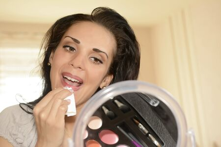 removing make up: young woman removing lipstick