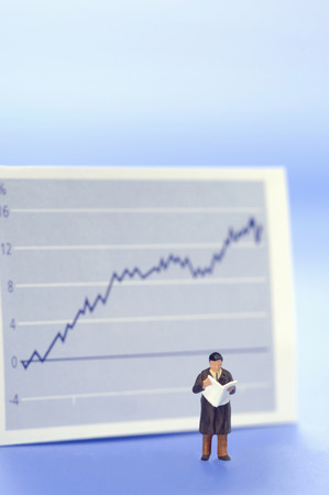 upturn: Figurine of businessman in front of graph Stock Photo