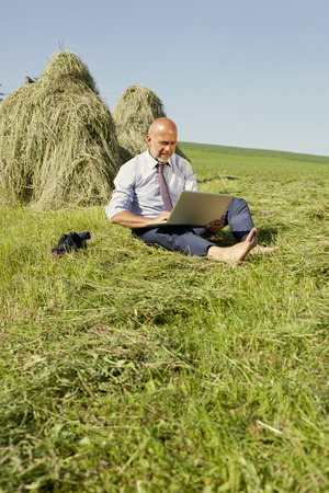 barefooted: Germany, Bavaria, businessman working with laptop outdoor Stock Photo