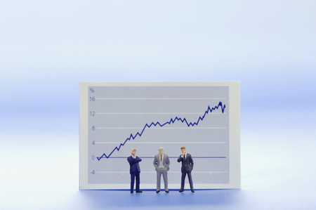 male likeness: Figurines of businessmen in front of graph