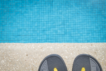 sandalias: Sandalias flip-flop en el borde de la piscina Foto de archivo