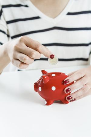 Woman saving money with red piggy bank Standard-Bild