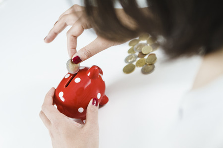 oldage: Woman saving money with red piggy bank Stock Photo