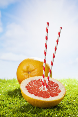 drinking straw: Grapefruit on grass, drinking straw, sunshine and clouds