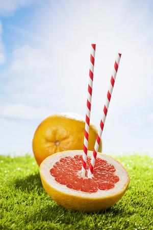 drinking straw: Pompelmo su erba, cannuccia, il sole e le nuvole