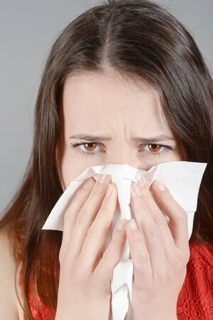 blowing nose: Young woman having cold, blowing nose