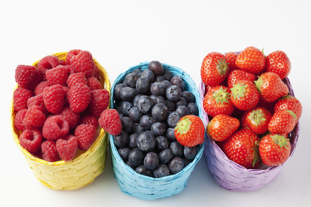 people in row: Forest berries, raspberries, blueberries and strawberries in baskets