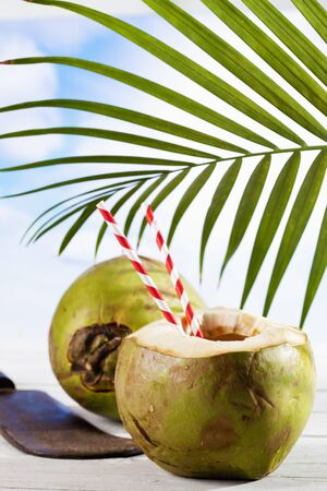cleaver: Coconut with drinking straws, old cleaver Stock Photo