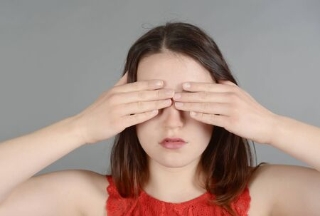 Young woman making hand gestures, see no evil