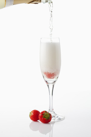 strawberry: Champagne glass with strawberry, pouring