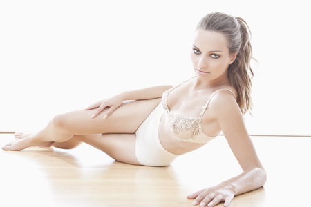 bra model: Young woman in beige lingerie lying against white background Stock Photo