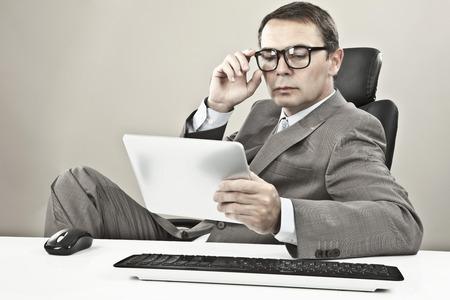 灰色背景: 灰色の背景に対してタブレット pc を見て実業家