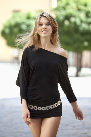 off the shoulder: Close up of young woman walking in black dress Stock Photo
