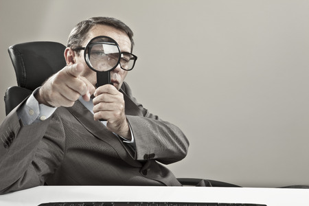 pedant: Close up of mature businessman looking through magnifying glass against grey background