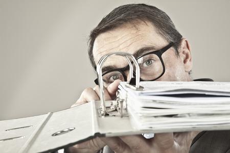 overstress: Close up of mature businessman looking through ring binder Stock Photo