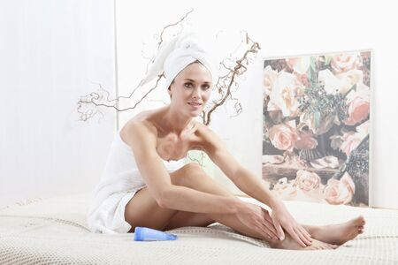 wrapped in a towel: Young woman wrapped in towel applying body cream