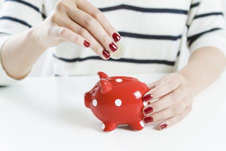 Woman saving money with red piggy bank Foto de archivo