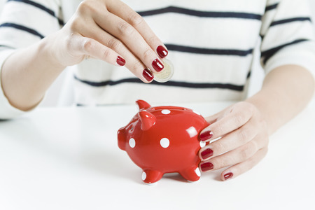 money savings: Woman saving money with red piggy bank Stock Photo