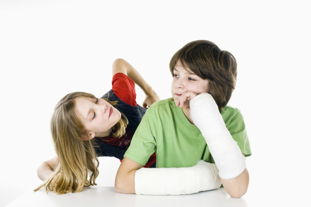 making fun: boy with two broken arms, girl making fun of him Stock Photo