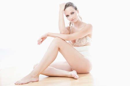 ropa interior femenina: La mujer joven en ropa interior de color beige sentado sobre fondo blanco Foto de archivo