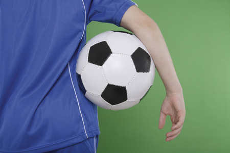 underarm: Close up of boy holding football underarm against green background Stock Photo
