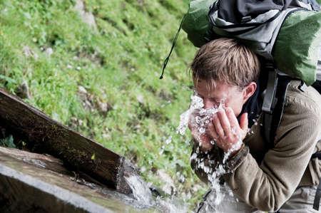 sediento: Hombre refrescante con agua en las montañas