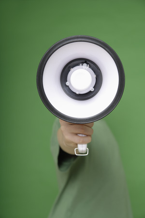 obscured face: Megaphone covering boys face against green background Stock Photo