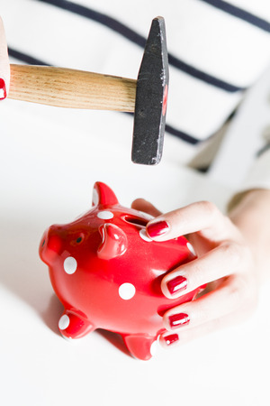 oldage: Red piggy bank and hammer held by woman