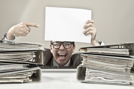 overstress: Close up of mature businessman holding blank paper and laughing Stock Photo