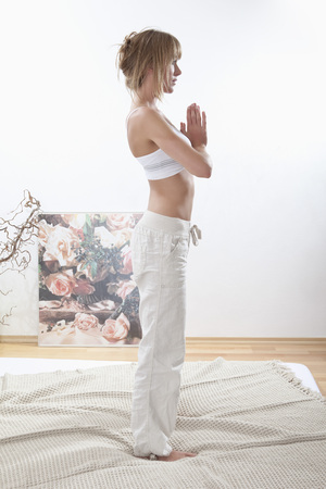 fringes: Young woman doing yoga exercise on bed in morning