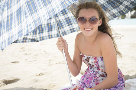 holidaymaker: Female teenager with umbrella at beach Stock Photo